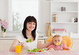 Charming brunette woman eating a salad next to her baby while si