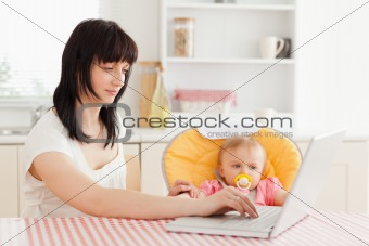 Attractive brunette woman relaxing with her laptop next to her b