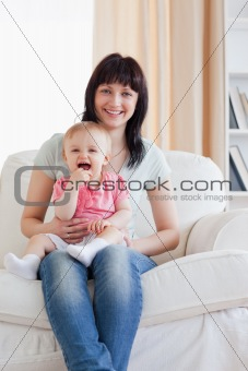 Attractive woman holding her baby in her arms while sitting on a