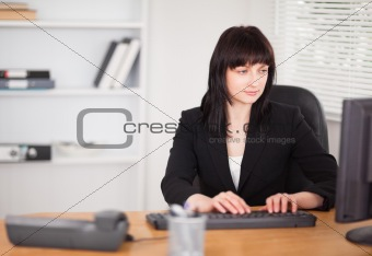 Beautiful brunette woman working on a computer while sitting at