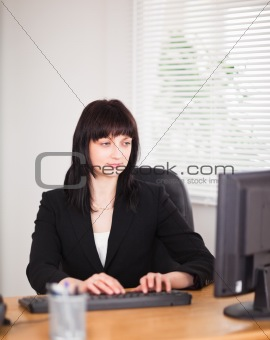 Attractive brunette woman working on a computer while sitting at
