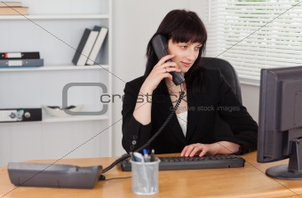 Attractive brunette woman on the phone while working on a comput