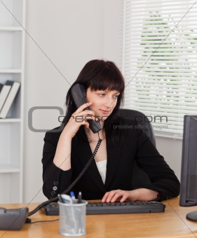 Beautiful brunette woman on the phone while working on a compute