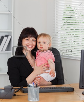 Attractive brunette woman posing while holding her baby on her k