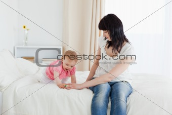 Beautiful brunette woman enjoying a moment with her baby while s