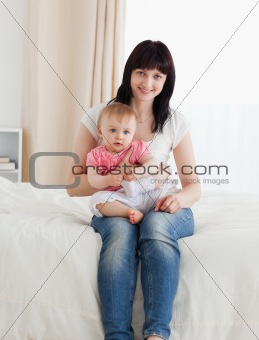 Beautiful brunette woman holding her baby on her knees while sit