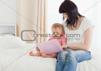 Beautiful brunette woman showing a book to her baby while sittin