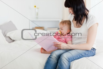 Charming brunette woman showing a book to her baby while sitting