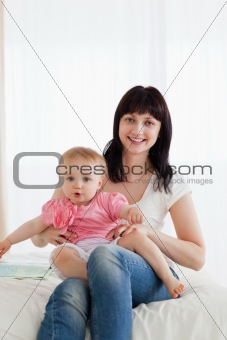 Attractive brunette woman holding her baby on her knees while si