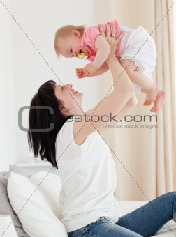 Attractive brunette woman playing with her baby while sitting on