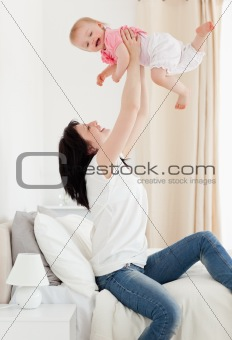 Beautiful brunette woman playing with her baby while sitting on