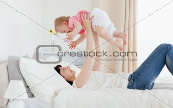 Charming brunette woman playing with her baby while lying on a b