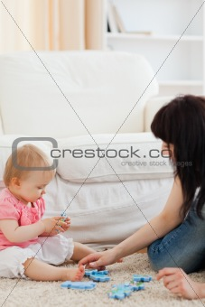 Attractive woman and her baby playing with puzzle pieces while s