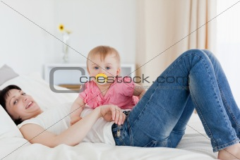 Beautiful brunette woman posing with her baby while lying on a b