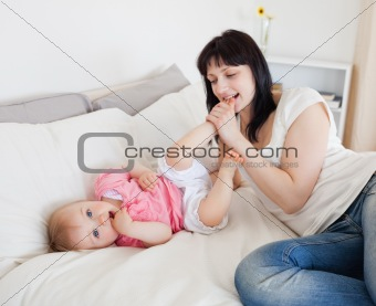 Attractive brunette female playing with her baby while lying on