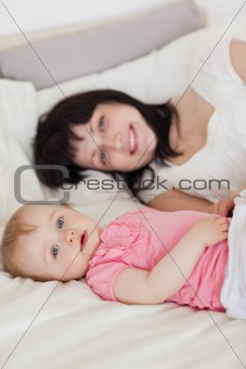 Attractive brunette female posing with her baby while lying on a