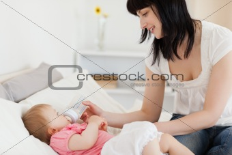 Attractive brunette female bottle-feeding her baby on a bed