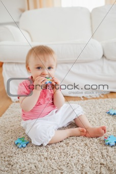Smiling baby playing with puzzle pieces while sitting on a carpe