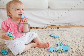 Blond baby playing with puzzle pieces while sitting on a carpet