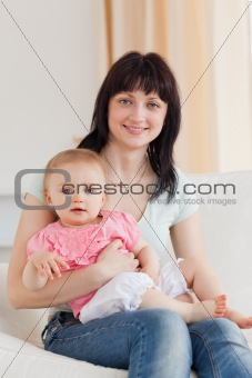Charming woman holding her baby in her arms while sitting on a s