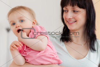 Cute woman holding her baby in her arms