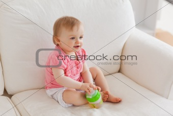 Blond baby playing with a ball while sitting on a sofa