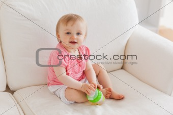 Baby playing with a ball while sitting on a sofa