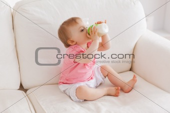 Baby bottle-feeding while sitting on a sofa