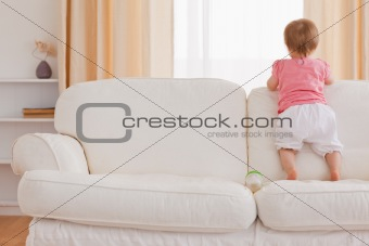 Blond baby standing on a sofa