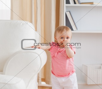Baby standing near a sofa