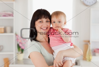 Beautiful woman holding her baby in her arms while standing
