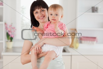 Charming woman holding her baby in her arms while standing