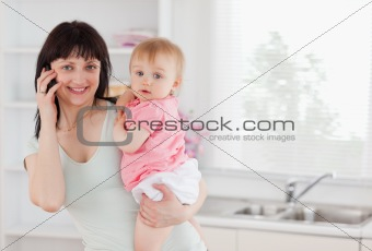 Beautiful woman on the phone while holding her baby in her arms