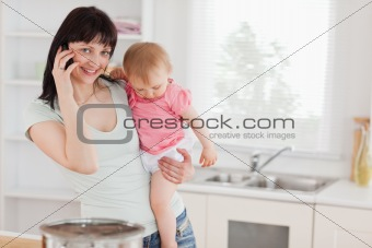 Attractive woman on the phone while holding her baby in her arms