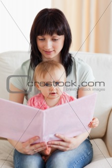 Attractive woman holding her baby and a book in her arms while s