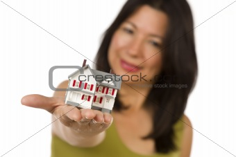 Attractive Multiethnic Woman Holding a Small House Out In Front of Her Isolated on a White Background.