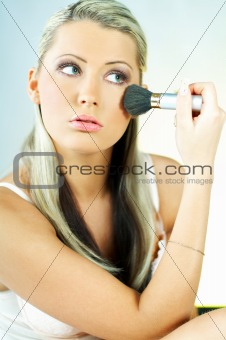 Portrait of blonde young sexy woman doing makeup