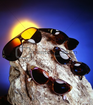 Four sunglasses over a nice stone