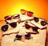 Six sunglasses over sand and stones