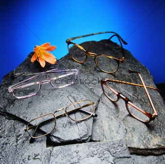 Four read glasses over black stones