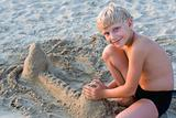 Smiling boy playing on sandy beach