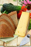 still life in a rustic style - cheese, tomatoes, cucumbers, rye bread on a wooden table