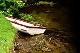 Small boat in a rural stream parked at the bank