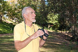 Active senior man birdwatching in wood