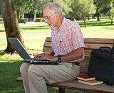 Senior man using laptop outdoors