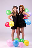 two beautiful women, with colored ballons, studio shot.