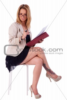 beautiful mature woman, secretary seated on a bench, reading some documents, isolated on white, studio shot