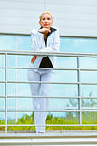 Portrait of smiling business woman leaning on railing at office building 