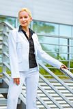 Smiling business woman standing on stairs at office building  and holding hand on railing 