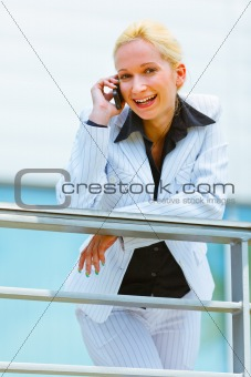 Smiling business woman leaning on railing at office building and talking on mobile